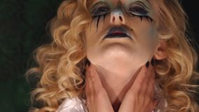 Close-up face of a girl with bright makeup for Halloween. The painted face of the girl in the form of a doll. Blonde with curly hair and terrible makeup witch stock footage