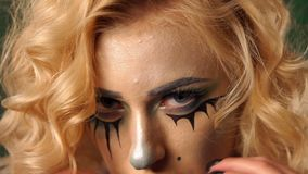 Close-up face of a girl with bright makeup for Halloween. The painted face of the girl in the form of a doll. Blonde with curly hair and terrible makeup witch stock video