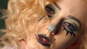 Close-up face of a girl with bright makeup for Halloween. The painted face of the girl in the form of a doll. Blonde with curly hair and terrible makeup witch stock video footage