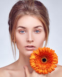 Close-up face of girl with flower in her hand. Close-up face of a girl with a flower in her hand Royalty Free Stock Photo
