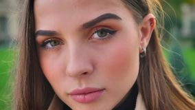 Close-up face of gorgeous caucasian woman looking calmly and straight at camera while standing outside is city, modern. Person, urban illustration stock footage