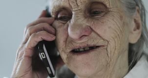 Close-up face of a grandmother with deep wrinkles talking on a mobile phone. Old woman is negotiating in the office stock video footage