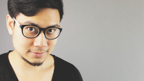 Close up face of a guy with eyeglasses. An asian man with black t-shirt stock image