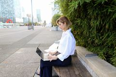 Close up face of woman typing with laptop outdoors. Close up face and hands of woman typing by laptop keyboard outdoors. Concept of typewriting skills and Stock Images