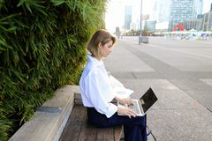 Close up face of woman typing with laptop outdoors. Close up face and hands of woman typing by laptop keyboard outdoors. Concept of typewriting skills and Stock Image