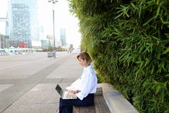 Close up face of woman typing with laptop outdoors. Close up face and hands of woman typing by laptop keyboard outdoors. Concept of typewriting skills and Stock Photos