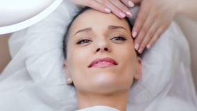 Close-up face of happy beautiful woman relaxing and enjoying massage at modern spa salon stock video