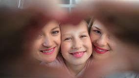 Close-up face happy child girl showing heart gesture by hand posing two lesbian kissing mother stock video footage