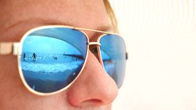Close-up face of a happy woman in sunglasses. The beach with the resting people is reflected in the glasses. 4k, slow stock video footage