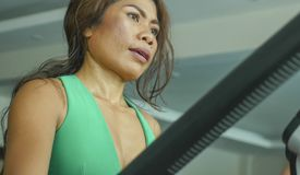 Close up face of young determined and focused Asian woman at gym doing workout in elliptical machine sweaty and tired in sport and royalty free stock photos