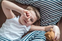 Close up face of Kid yawning and holding teddy bear, Sleepy child yawning and looking at cameta, Head shot tired child get a cold. During weather change royalty free stock photography