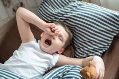Close up face of Kid yawning and holding teddy bear, Sleepy child yawning and looking at cameta, Head shot tired child get a cold. During weather change stock images