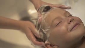 Close up face little boy while washing hair and head in children hairdressing salon. Hairdresser hand wash head. Children barbershop salon. Hairstylist washing stock video