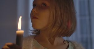 Close-up face of little Caucasian girl holding candle and shaking her head. Portrait of a child scared by something