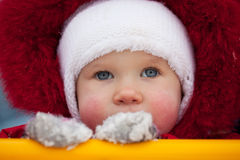 Close-up of the face a little girl. In red jumpsuit Stock Images