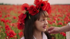Close-up face of little girl with wreath of red poppy flowers on her head. Mother straightens her hair stock video footage