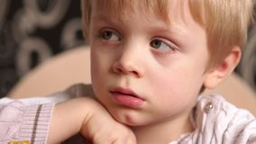 Portrait of sad little boy in the kitchen at table. Close-up of the face of a little sad boy, he sits at the table in the kitchen. Slow motion stock video footage
