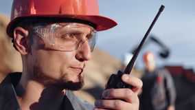 Close-up face male engineer in glasses and helmet talking using walkie talkie at construction site stock video