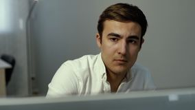 Close-up face portrait of serious focused trader looking at screen stock online. In white office. Casual man using computer sitting at the office desk. Busy stock footage