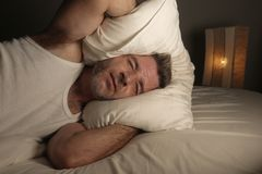 Close up face portrait of sleepless and awake attractive man with eyes wide open at night lying on bed suffering insomnia sleeping royalty free stock photography