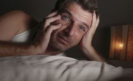Close up face portrait of sleepless and awake attractive man with eyes wide open at night lying on bed suffering insomnia sleeping stock photos