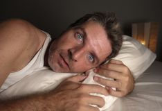 Close up face portrait of sleepless and awake attractive man with eyes wide open at night lying on bed suffering insomnia sleeping royalty free stock photos