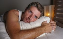Close up face portrait of sleepless and awake attractive man with eyes wide open at night lying on bed suffering insomnia sleeping stock image