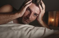 Close up face portrait of sleepless and awake attractive man with eyes wide open at night lying on bed suffering insomnia sleeping royalty free stock image