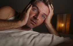 Close up face portrait of sleepless and awake attractive man with eyes wide open at night lying on bed suffering insomnia sleeping royalty free stock images