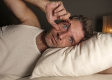 Close up face portrait of sleepless and awake attractive man with eyes wide open at night lying on bed suffering insomnia sleeping stock photo