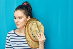 Close up face portrait of smiling teen girl with closed eyes hol. Ding hat. Blue wall background Stock Photo
