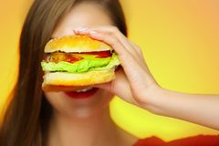 Close up face portrait of smiling woman holding big burger. Yellow background. Smile with teeth Royalty Free Stock Photo