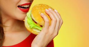 Close up face portrait of smiling woman holding big burger. Yellow background. Smile with teeth Stock Photo