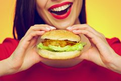 Close up face portrait of smiling woman holding big burger. Yellow background. Smile with teeth Royalty Free Stock Photos