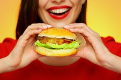 Close up face portrait of smiling woman holding big burger. Yellow background. Smile with teeth Royalty Free Stock Image