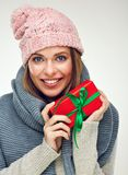 Close up face portrait of smiling woman wearing winter hat and s. Carf holding red gift box Royalty Free Stock Photos