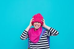 Close up face portrait of toothy smiling young woman wearing knitted pink hat and scarf. A happy smiling woman on a turquoise background in the studio. Copy Royalty Free Stock Photo