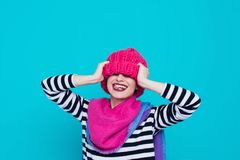 Close up face portrait of toothy smiling young woman wearing knitted pink hat and scarf. A happy smiling woman on a turquoise background in the studio. Copy Stock Photo