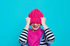 Close up face portrait of toothy smiling young woman wearing knitted pink hat and scarf. A happy smiling woman on a turquoise background in the studio. Copy Royalty Free Stock Photography
