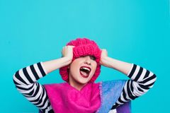 Close up face portrait of toothy smiling young woman wearing knitted pink hat and scarf. A happy smiling woman on a turquoise background in the studio. Copy Royalty Free Stock Photos