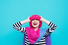Close up face portrait of toothy smiling young woman wearing knitted pink hat and scarf. A happy smiling woman on a turquoise background in the studio. Copy Royalty Free Stock Images