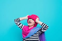 Close up face portrait of toothy smiling young woman wearing knitted pink hat and scarf. A happy smiling woman on a turquoise background in the studio. Copy Stock Image