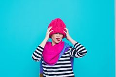 Close up face portrait of toothy smiling young woman wearing knitted pink hat and scarf. A happy smiling woman on a turquoise background in the studio. Copy Royalty Free Stock Image