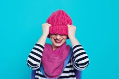 Close up face portrait of toothy smiling young woman wearing knitted pink hat and scarf. A happy smiling woman on a turquoise background in the studio. Copy Stock Images