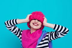 Close up face portrait of toothy smiling young woman wearing knitted pink hat and scarf. A happy smiling woman on a turquoise background in the studio. Copy Stock Photos