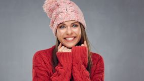 Close up face portrait of toothy smiling young woman wearing red. Sweater with pink knitted hat Stock Image
