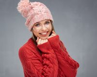 Close up face portrait of toothy smiling young woman wearing red. Sweater with pink knitted hat Royalty Free Stock Photo