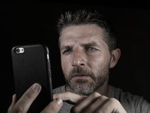 Young attractive and confident white man with blue eyes using online dating app or internet social media on mobile phone isolated. Close up face portrait of stock photos