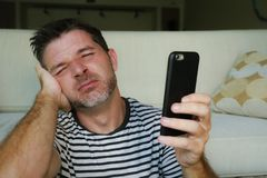 Close up face portrait of young attractive and stressed man using mobile phone desperate and exhausted in frustrated and confused stock image