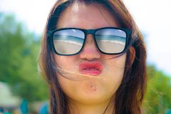 Close up face portrait of young beautiful Asian woman wearing sunglasses with tropical beach sea and sand reflection on the glasse Royalty Free Stock Images